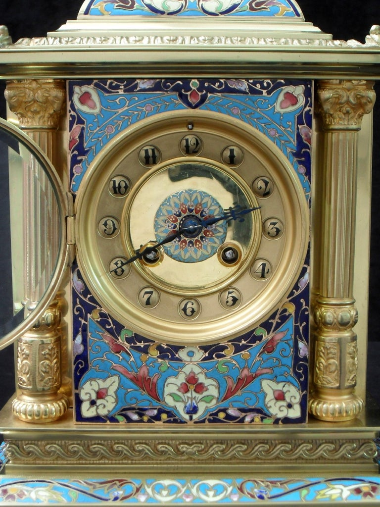 An extremely good quality French Belle Époque brass mantel clock with a beautiful champlevé coloured enamel front and mouldings. The clock has fluted Corinthian columns to the front corners with decorative ram's head capitals and scroll relief
