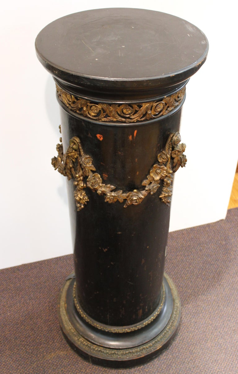 French Belle Époque column or pedestal in ebonized wood, with decorative ormolu floral garlands and friezes on the base and top. The piece was made in France during the 1890s and is in great vintage condition with age-appropriate wear.