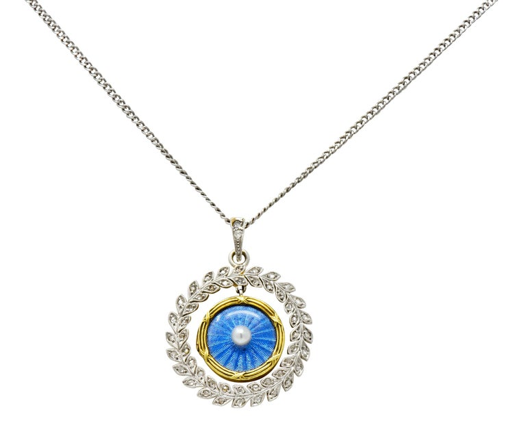 Locket centers a round button pearl measuring approximately 3.0 mm; cream in body color with excellent luster  Surrounded by cornflower blue enamel featuring a scalloped radiating motif encased by glass and a ridged gold surround  Back is clear