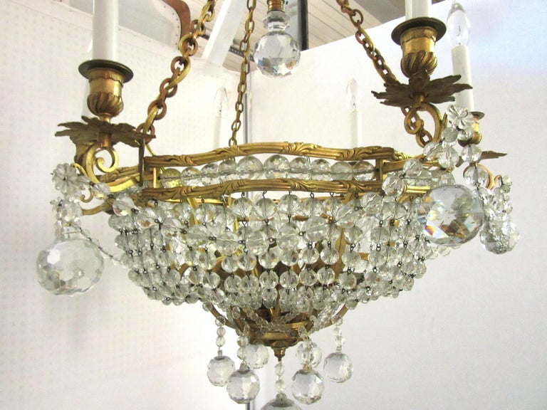 French Belle Époque gilt bronze chandelier with twelve lights. The piece has 18 cut crystal faceted spheres and numerous cut glass garlands. In great antique condition with age-appropriate wear and use. Recently restored to its original state.