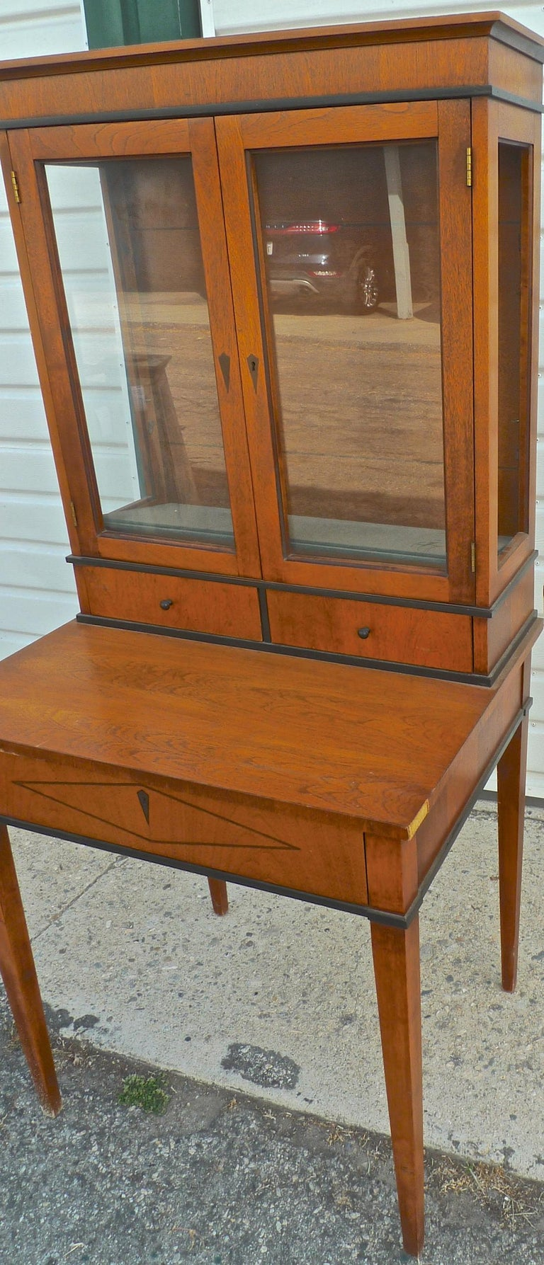 French Biedermeier 1940s birchwood desk with three drawers and two glass cabinet doors and two glass shelves.
