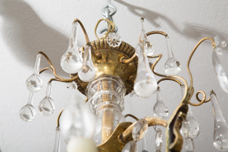 This is a unique French gilt bronze birdcage chandelier hung overall with tear-drop crystal pendants and elliptical crystal ropes. The fixture is centered by a crystal encased support, early 20th century.