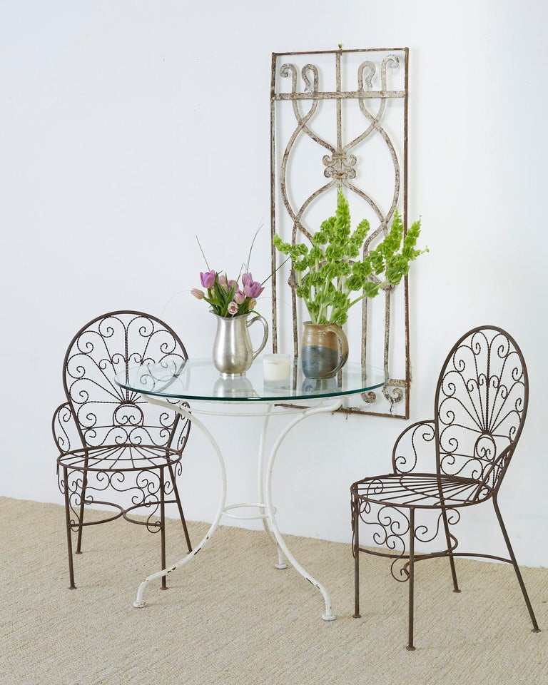 Rustic French bistro style garden or patio table featuring a painted metal frame topped with a round pane of glass. Supported by curved legs conjoined in the center of the hour glass shape with a round stretcher. Ends with round disk feet. Lovely