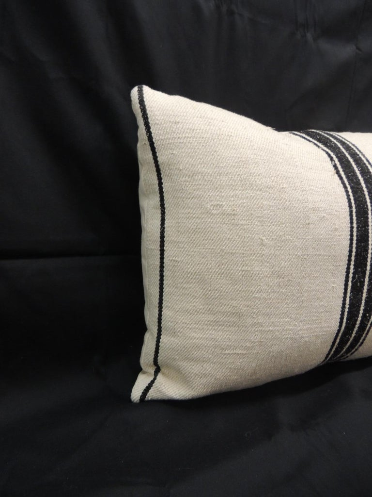19th century French stripes lumbar decorative pillow in natural and black. Decorative pillow textile show vertical stripes on tan with a woven homespun textile. French decorative cushion finalized with natural linen backing. Throw pillow in shades