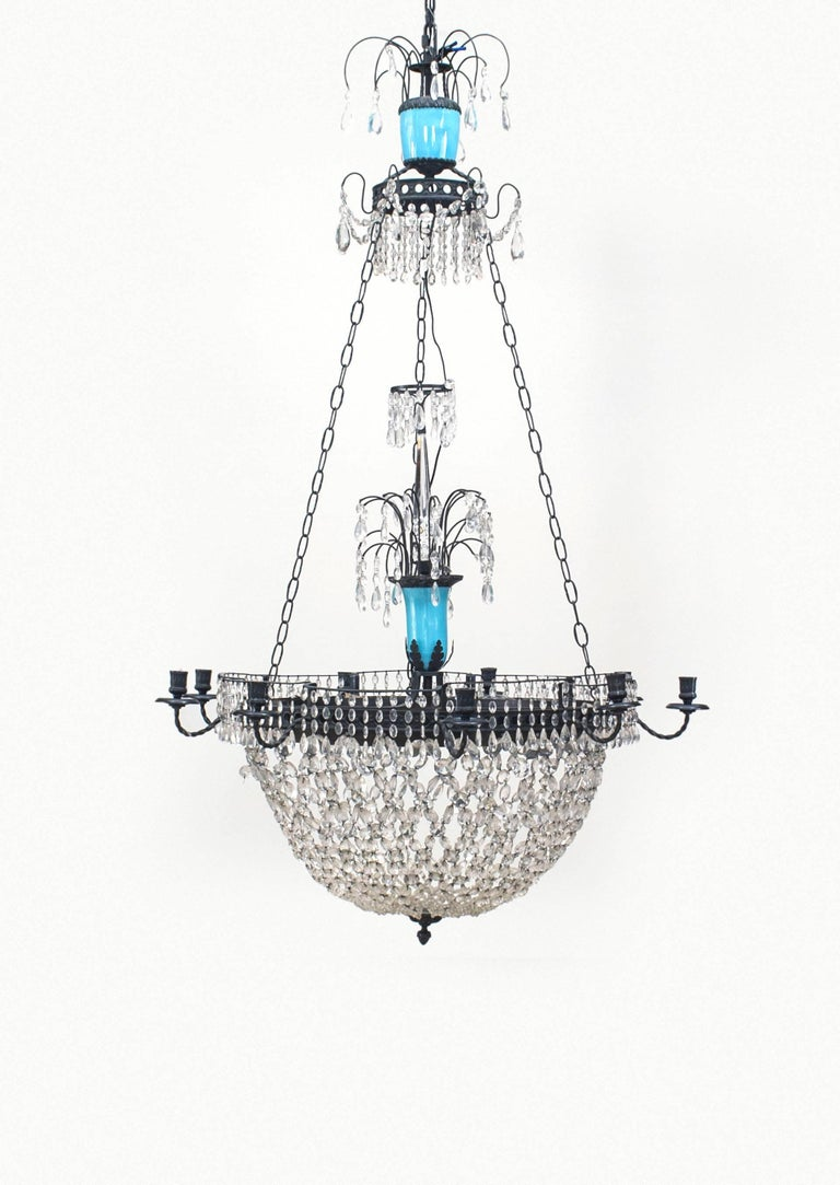 Nineteenth century French chandelier featuring a segmented opaline glass stem above a round, bowl-shaped crystal bottom rimmed with nine candleholder arms and culminating in an iron finial.