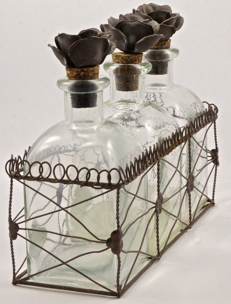 Lovely set of three French storage bottles with metal flower and cork stoppers, contained in an intricate metal wire basket holder. The flowers and basket are painted in mushroom brown with lighter coloured flecks. The bottles are made from the old