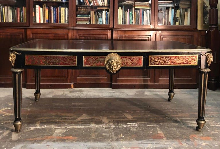 Exceptional French Boulle bureau plat has the English feel of a library table with the four rams head mounted bronze fluted legs terminating in a bronze caster stylized as a beehive. The Boulle marquetry writing desk is finished on both sides with