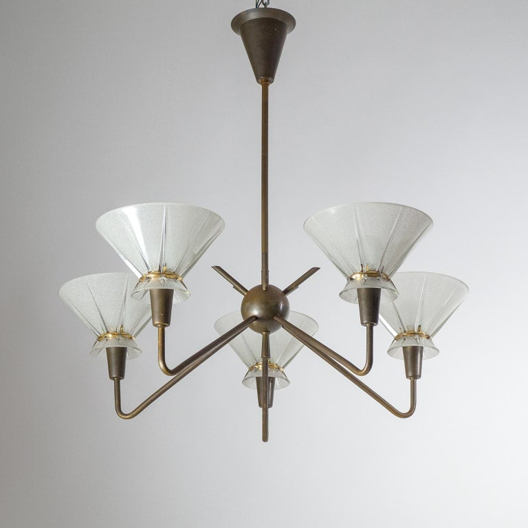 Beautiful five-arm brass and glass French modern chandelier from the 1950s. Very well crafted with dark patinated solid brass hardware and textured glass diffusers with gold paint decor. Each arm has a brass E14 socket with new wiring. Measures: