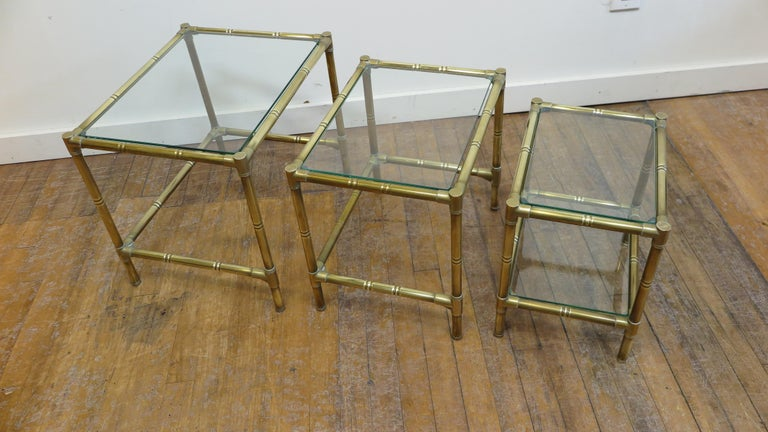 French midcentury brass and glass set of 3 nesting tables. Modernist brass faux bamboo styled nesting tables. Tables are high quality brass construction with brass joining's. Very good condition. Patina to the brass, all the glass tops are new. The