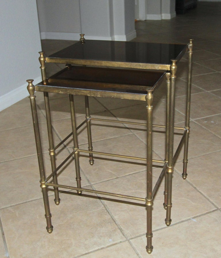 Pair of brass or bronze nesting tables with antiqued bronzed mirrored inset tops, can be used as side table. Nice bronzed aged patina to brass finish.  Table #1 - 16 W x 12