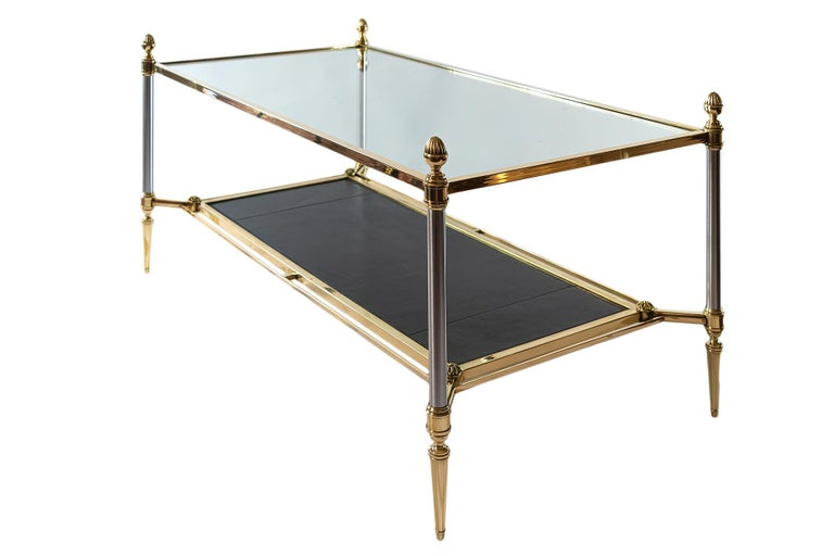 Midcentury brass coffee table. The top is covered with transparent glass and down shelve is decorated with black natural leather in brass frame.