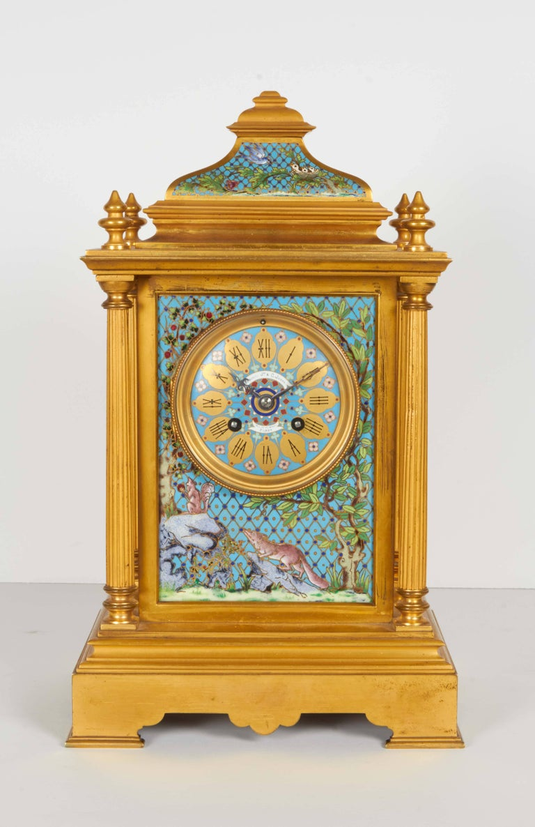 A magnificent and unusual French ormolu and cloisonne / champleve enamel clock garniture, comprising of five pieces, circa 1890.  A clock, a pair of vases and a pair of five-light candelabra finely decorated with brightly colored panels. The clock