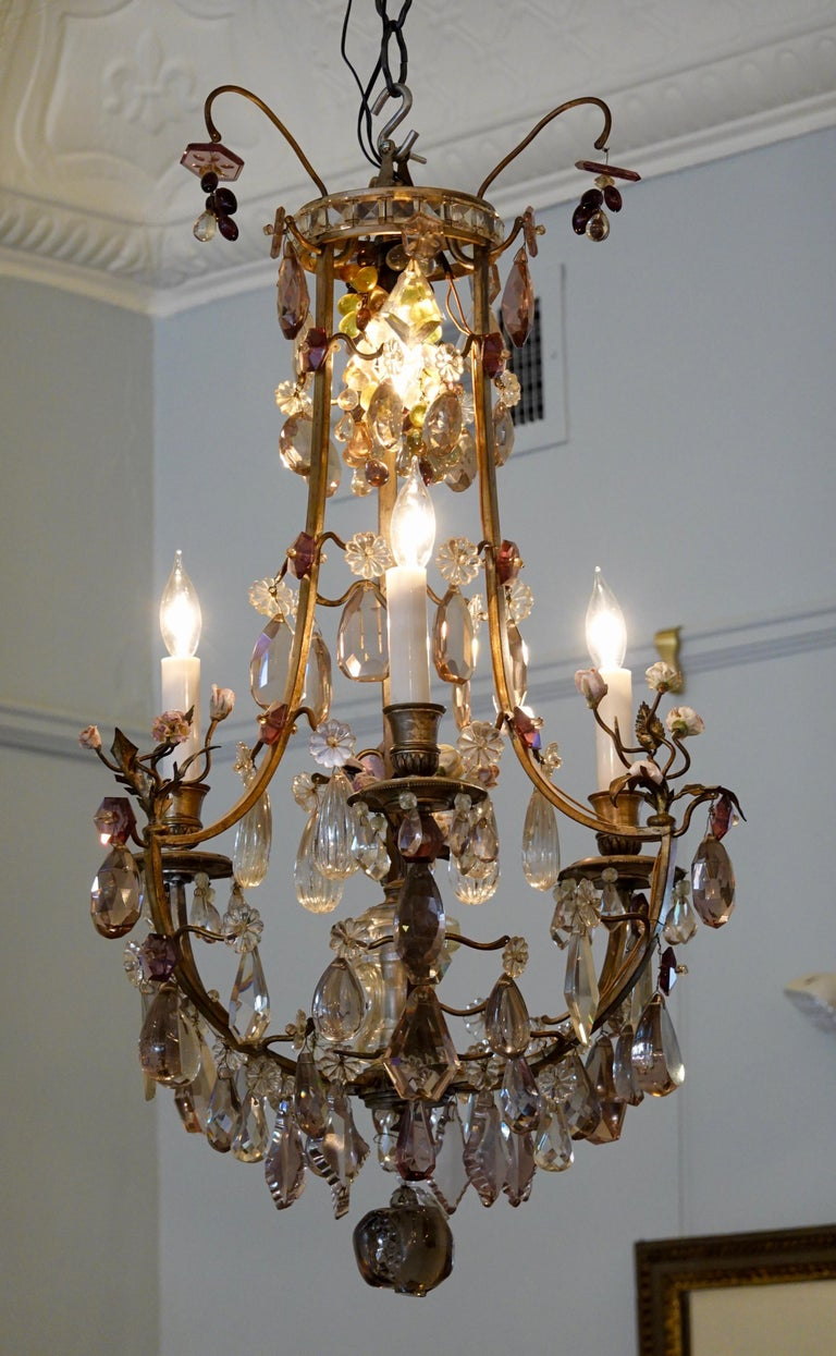 French cage-form bronze and crystal chandelier with porcelain flowers in the Louis XVI style, electrified with four lights. This chandelier features three bunches of porcelain flowers on the main arms, with a central spray of porcelain flowers in