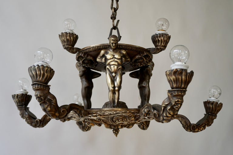 A remarkable two tier bronze six light French Hollywood Regency chandelier, the upper part inspired by Wiener Werkstätte Art Deco designs showing three male nude figures supporting a fountainlike structure, the lower part decorated with medallions