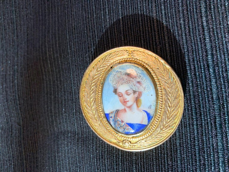 A cast bronze brooch by French Parisian Art Jeweler Line Vautrin (1913-1997) circa 1950s. The small lovely bronze pieces features a medallion insignia design with olive branch wreath surrounding an enamel portrait of a royal female, presumably Queen