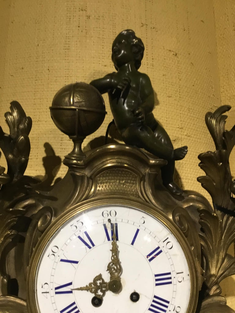 Large cartel clock in bronze with a patinated putto that sits at the crest of this exceptional clock. Flourishes and foliate designs grace the sides of the circular clock face that is made of white Enamel with blue Roman numerals. The pendulum and