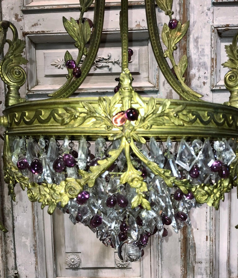 19th century French bronze, crystal, and amethyst chandelier. The frame superbly decorated with acanthus leaves, laurel and berries, flamed torches, and garland swags. Adorned with small crystal rosettes, kite-shaped prisms, and icicle drops.