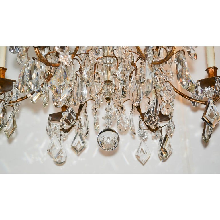 Stunning high style French gilt bronze and crystal chandelier. Lavishly decorated with multiple graduated tiers of fancy crystals, including almond, tear-drop, kite, and diamond prisms. Accented with an abundance of crystal rosettes and having an