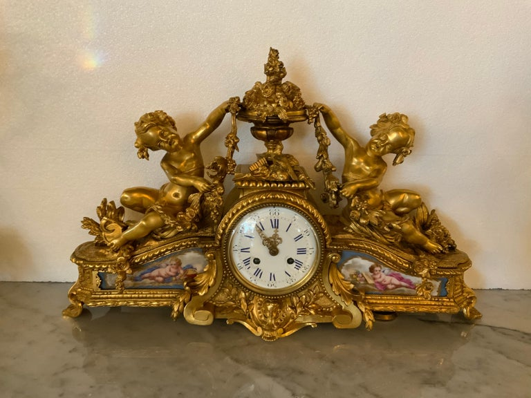 Bronze gilt French mantel clock with Sevres style porcelain painted with cherubs. A centered urn At the crest with floral and foliate design. A petite bird centered at the top. Two gilt cherubs Are at each side supporting garlands of flowers.