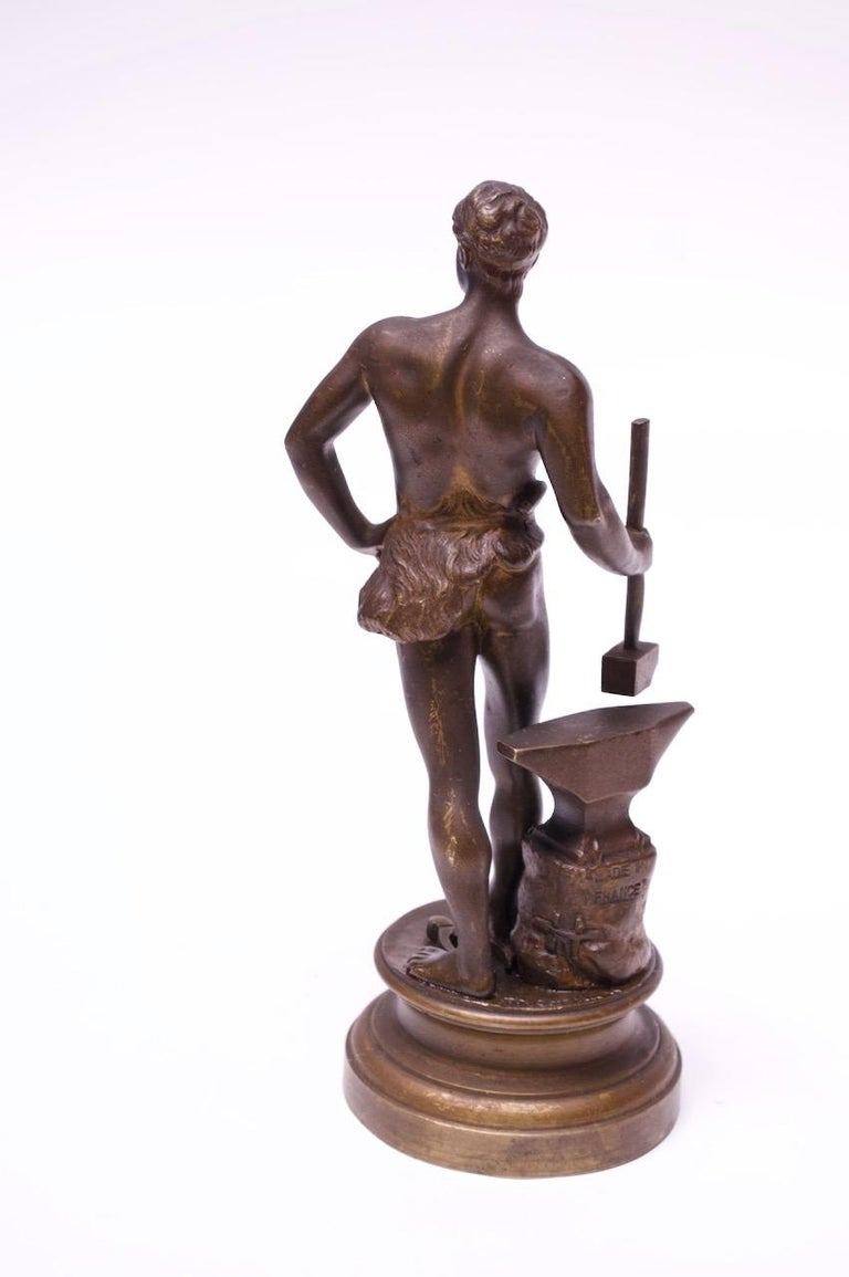 Circa 1920s bronze sculpture by Maurice Constant (France 1892-1970). Likely, a depiction of a young Hephaestus / Vulcan, the blacksmith god of fire and forge, surrounded by his signature tools: hammer, anvil, and tongs. Signed