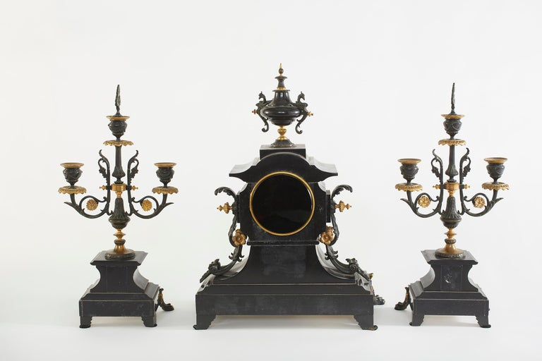 French bronze & polish black marble with applied bronze trim three piece clock garniture set. The clock surmounted by an urn flanked & griffins. Clock face with gold Roman numerals and spade hands. Illegible signature, brass 8 day movement with rack