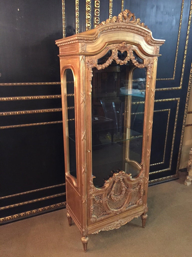 French cabinet in Louis Seize style  Solid beech, gilded. Rectangular, three-sided, faceted beveled, one-door body on conical legs. The door is partially provided with wickerwork. The front, corners and sides are decorated with carved, Classic