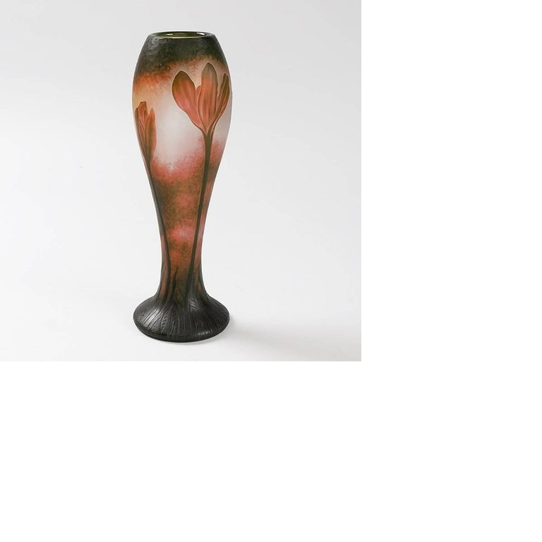 A French cameo glass vase by Daum. The vase, with martelé background, has red wheel-carved lily flowers rising on green stems from its carved green base.