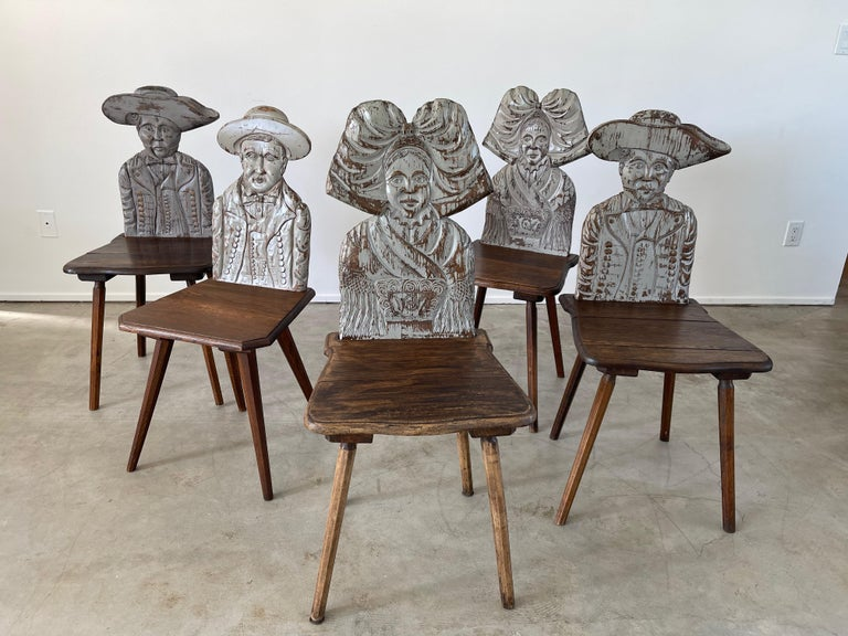 Unique intricately carved dining chairs with heads in different shapes Wonderful patina and sold individually.  Great as a corner chair!