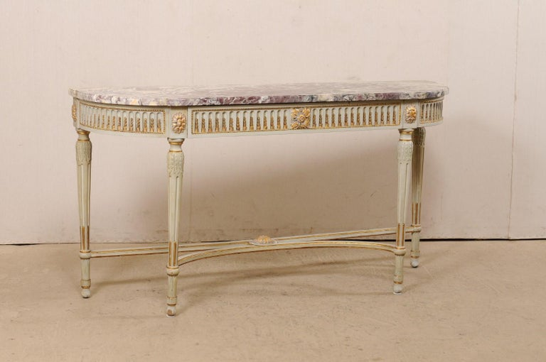 A lovely French marble top console table, with carved and gilt accents, from the turn of the 18th and 19th century. This antique table from France features an oblong shaped top with flattened backside and curved and stepped out shaped front. The