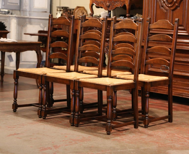This elegant set of country chairs was crafted in France, circa 1990. Carved from solid oak, each chair has a tall back with four ladders across and two top finials. The seats have a woven rush surface, four carved, turned legs, and a pitched back,