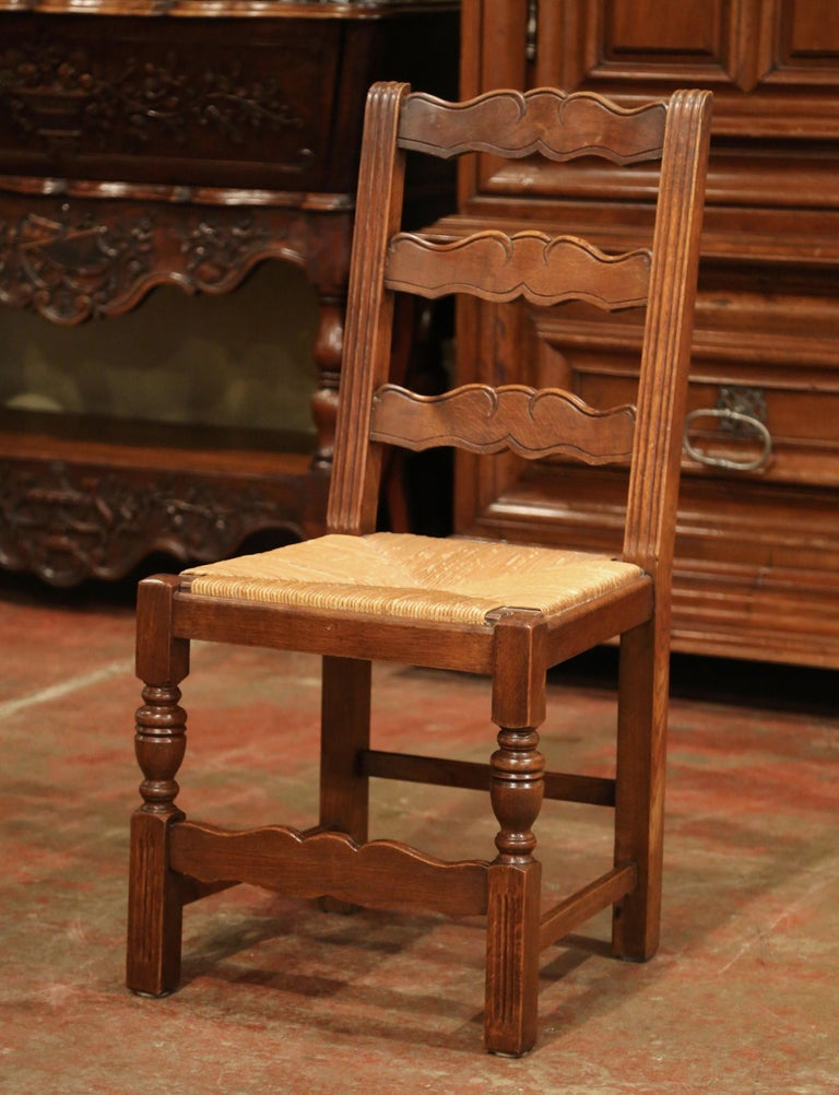 This elegant set of country chairs was crafted in France, circa 1980. Carved from solid oak, each chair has three ladders across the pitched back which give each chair great support and comfort. The seat has woven rush surface over four carved and