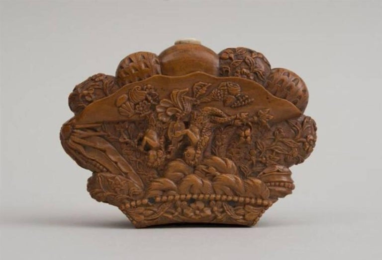 The elaborately carved snuff box with a scene of two mermaids on the cover and deeply carved shell on the reverse.
