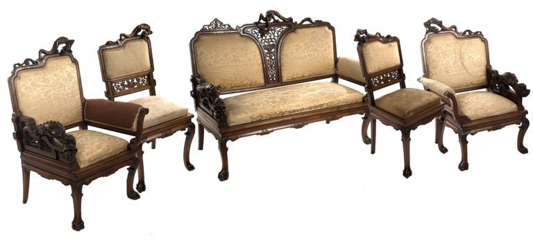 A carved walnut and gold silk upholstered French Chinoiserie seating set comprised of a sofa, two side chairs and two armchairs in the style of Gabriel Viardot. The carved frame of the side chairs have shaped square backs mounted with an elongated