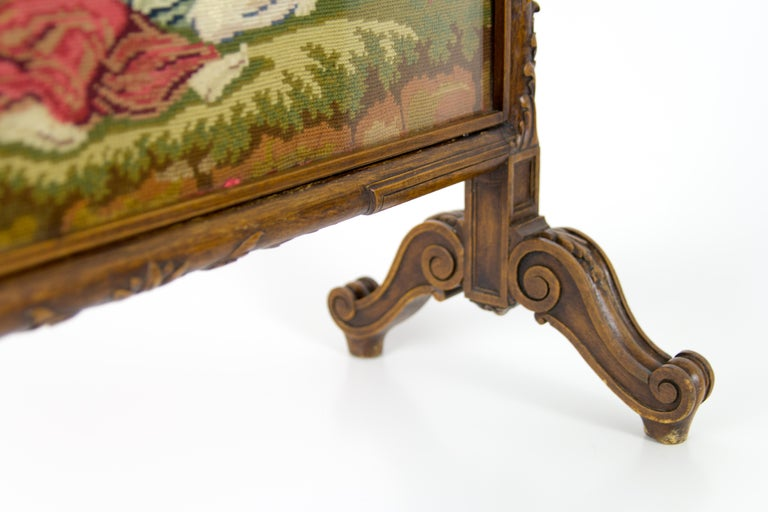 French needlepoint and carved walnut frame fire screen. Needlepoint panel under glass screen, on reverse a red velvet fabric. Dimensions: Height 77 cm / 30.31 in; width 55 cm / 21.65 in; depth 25 cm / 9.84 in.