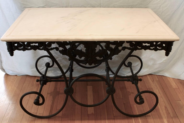 French cast iron and marble top Baker's table. The marble is white with some veining. The pierced cast iron apron features a stylized acanthus leaf in the front and back, and nice scrolling details around the perimeter, with finials in each corner.