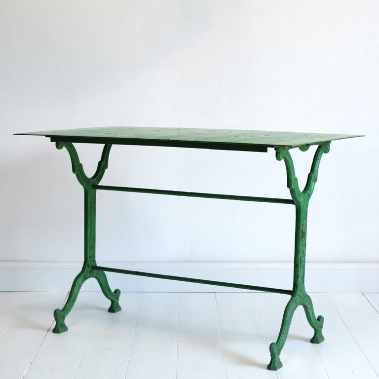 A very good quality French 19th century cast iron garden table by Groeff of Toulon. Layers of old paint with the most prominent being a striking but very tasteful green. Two very well-cast decorative trestle type supports united by twin rod