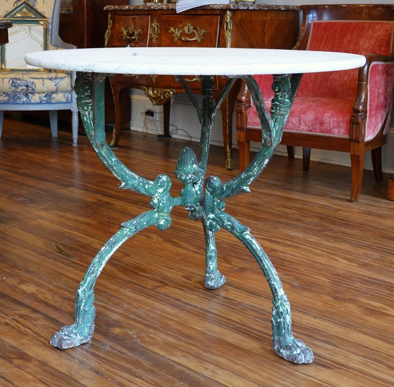This French cast iron garden table has an old green painted finish and features a highly decorate tripod base with paw feet, an acorn finial, and the top of each leg terminating with a caryatid's head. The white Carrera marble top with grey veining