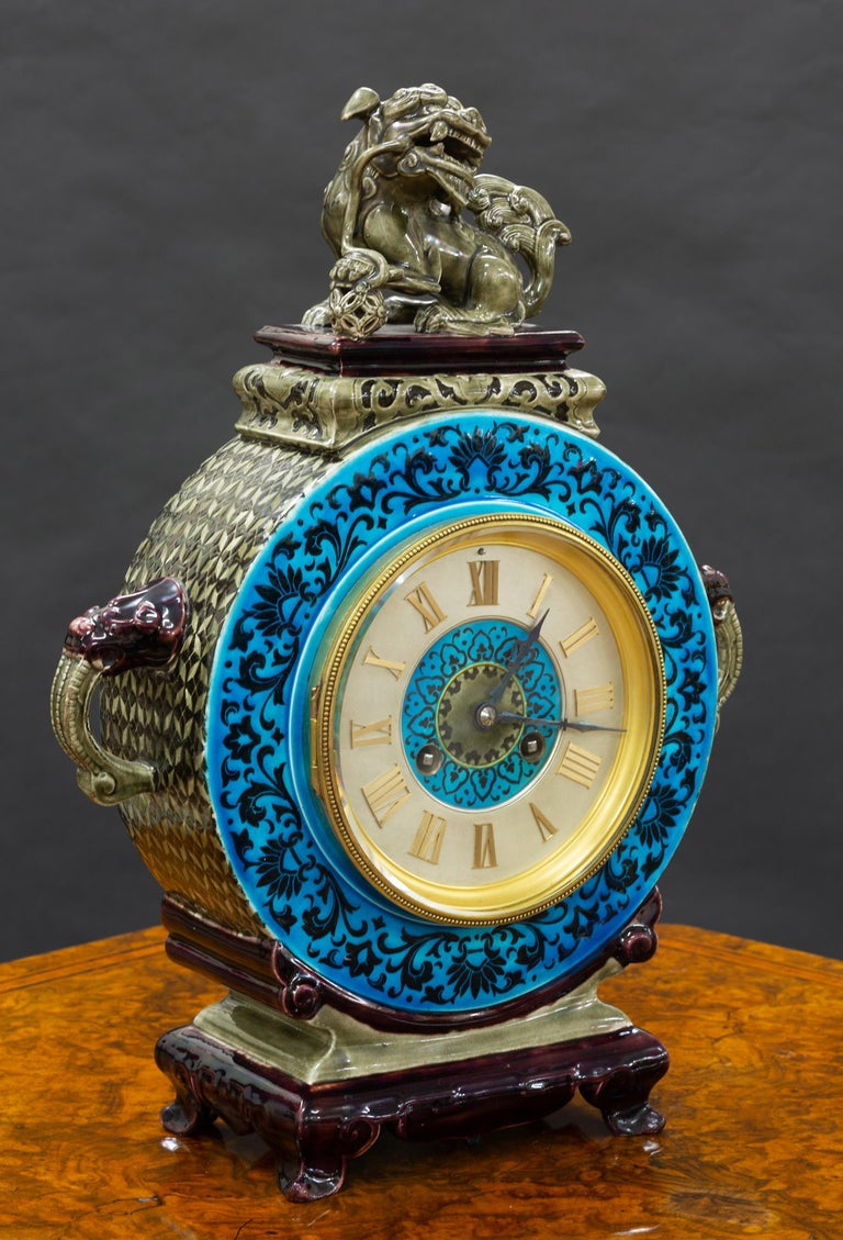 French ceramic clock with Chinese decoration standing on outswept feet with purple and turquoise glazed decoration and lions head 'carrying' handles surmounted by a Foo dog resting his foot on a lattice work ball.  Raised beaded decorated gilded