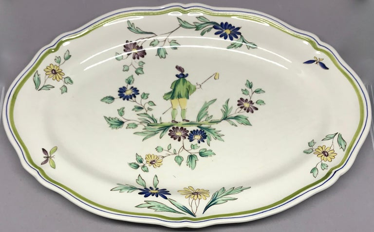 French ceramic painted chinoiserie platter. Vintage Longchamps shaped oval platter with hand painted figure amongst flowers and butterflies. France, mid-20th century. Dimensions: 14