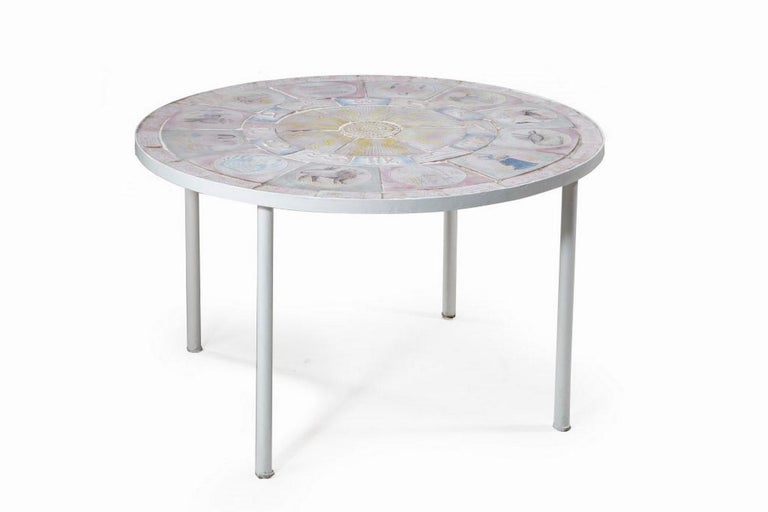 Table with tiled top depicting the signs of the zodiac, with white lacquered metal legs.