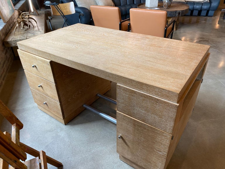 Partners desk of French white oak with cerused finish. Cabinetry on both sides with ample storage, it can be floated in a room. Plated metal rods create foot rests at base. Well constructed and heavy. Late Art Deco or early Mid-Century Modern