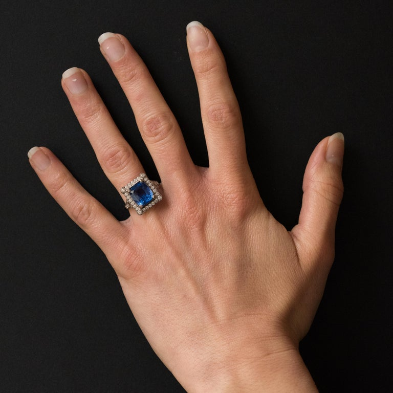 18K white gold ring, eagle's head hallmark. This splendid rectangular shaped sapphire and white gold ring boasts a cushion cut Ceylan Blue sapphire held by 4 claws surrounded by brilliant cut diamonds of which the 4 corner ones are surmounted by a