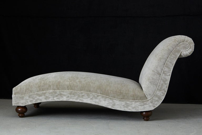 Gorgeous 1930s French chaise longue with a puristic design and a lovely curved shape and mounted on ball feet. The piece has been newly upholstery in a beige stria velvet. A very comfortable and great statement piece.