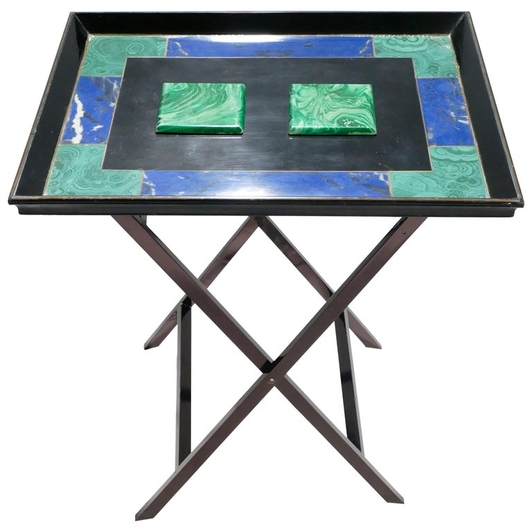 This folding tray table is a rare and unique piece from Christian Dior's, 1970s line of furniture. For both the tray and the legs, wood is painted a smooth black. While the structure of the tray displays the traditional lines of Neoclassism, the