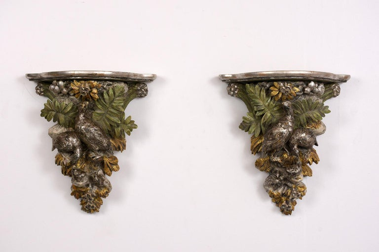This rare 1840s pair of French Black Forest giltwood brackets. The set has excellent hand carved details depicting two birds resting on branches surrounding by leaves and flowers. These brackets are hand painted in green color and have a silver and