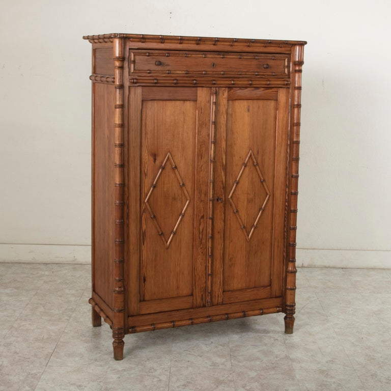 This turn of the 20th century French colonial style pitch pine armoirette features faux bamboo corners and edges constructed of maple. Its two paneled doors are detailed with faux bamboo diamonds and open to reveal an interior with three adjustable