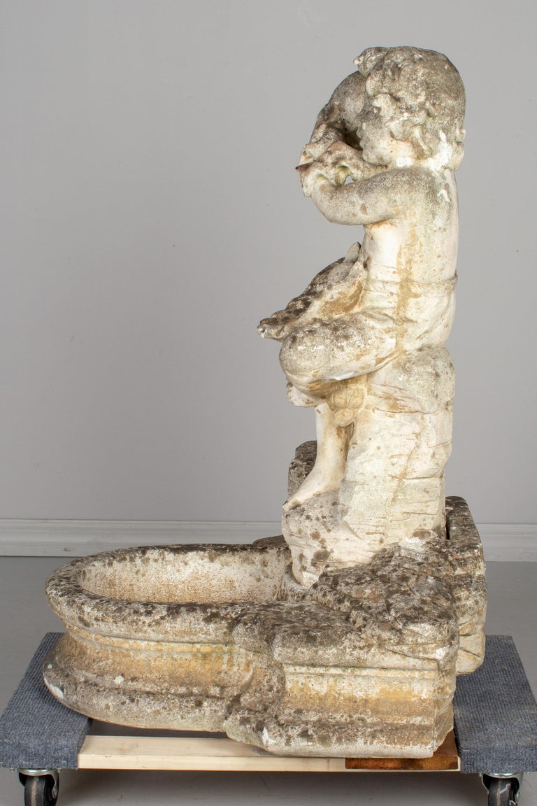 A French cast composite stone garden fountain from the Southeast of France featuring a seated cherub holding a large seashell to his ear. Water flows from from the seashell to the clamshell in his lap and pools into the basin below. Beneath the