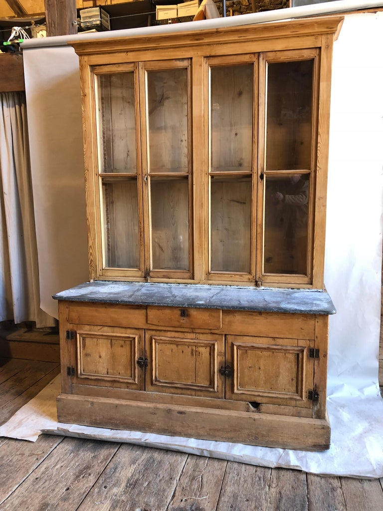 A French country kitchen cabinet in 2 parts, in stripped pine with glazed doors and a zinc work surface, late 18th century. Four glazed doors with adjustable shelves in upper cabinet which rests on a zinc-top lower cabinet with drawer and lower