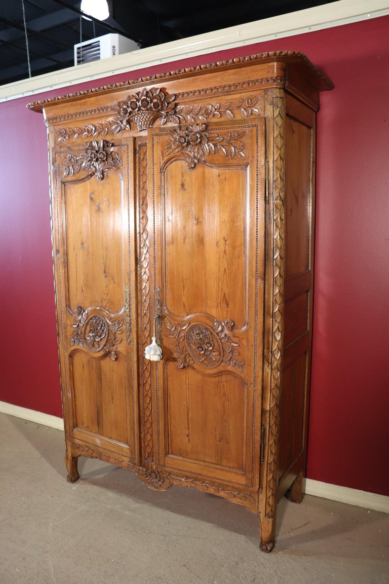 This is a beautifully carved pine French country armoire, circa 1840. The armoire has been converted to use for a television but that was commonly done in the early 2000s as many already know. The armoire features fine carving and great antique