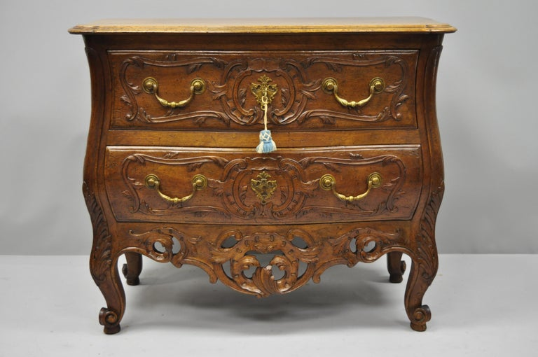 French Country carved walnut bachelor chest. Item features solid wood construction, beautiful wood grain, distressed finish, finely carved details, working lock and key, two dovetailed drawers, cabriole legs, and solid brass hardware, circa early